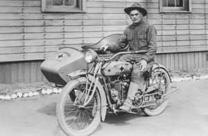 Private Henry M. Walsh poses on a motorcycle.