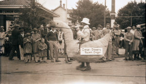 A man wears a goose costume in a parade.